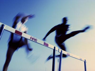 Low Angle View Of Athletes Jumping Over Hurdles