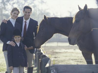 Portrait of a Family Standing Beside Two Horses