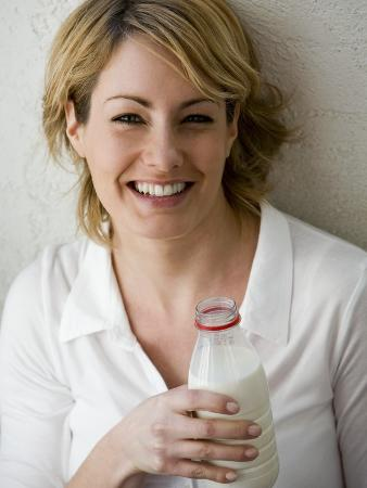 Young Woman Holding a Bottle of Milk in Her Hand