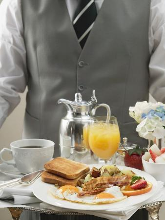 Butler Serving Breakfast Tray with Bacon, Eggs and Toast