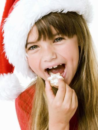 Girl in Father Christmas Hat Eating Biscuit