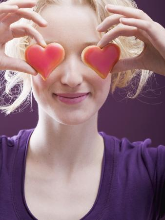 Young Woman Holding Hearts in Front of Her Eyes
