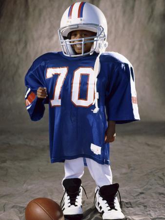 Boy in an Oversized Football Uniform Wearing a Helmet