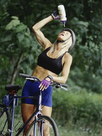 Blond Bicyclist Cooling Off with Bottled Water