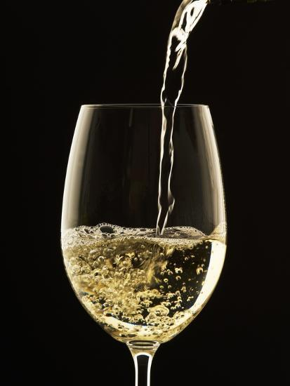 White Wine Pouring from Bottle into Glass Photographic ...
