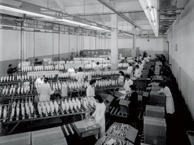 Interior of a Textile Factory, Numerous Workers in White Smocks are Packing Large Reels of Thread