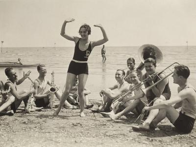 A Young Woman, Surrounded by Musicians, Dances on a Beach of the Lido of Venice