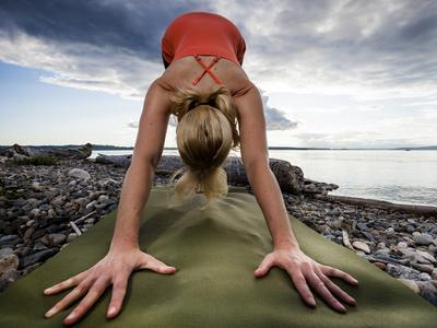 Lisa Eaton Holds a Downward Dog Yoga Pose on the Beach of Lincoln Park - West Seattle, Washington