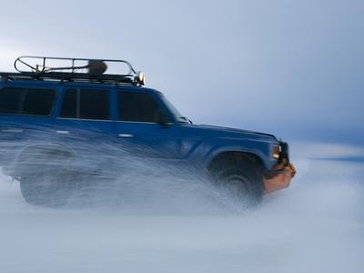 Travelers Drive over a Flooded Salt Flat in Bolivia