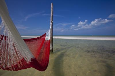A Red Hammock Spread Out by the Wind Swings Above the Water During Low Tide, Hobox Island, Mexico