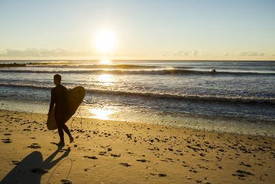 A Young Male Surfer Walks Along the Beach at End of Long Beach Island, New Jersey