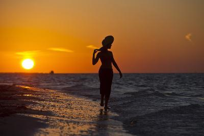A Silhouette of a Woman Wearing a Hat Walking in the Surf at Sunset on Holbox Island, Mexico