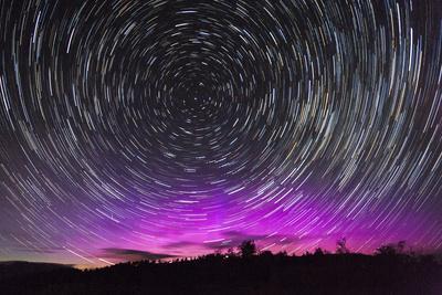 Stars Swirl around Polaris as Northern Lights Dance on the Horizon over Jackson Hole, Wyoming