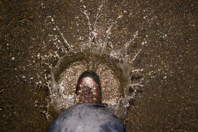 A Hiking Boot Splashing in a Puddle in a Parking Lot in Boulder, Colorado