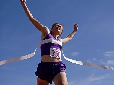 Female Runner Celebrates Victory at the Finish Line