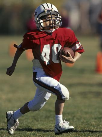 8 Year Old Boy Running with the Football