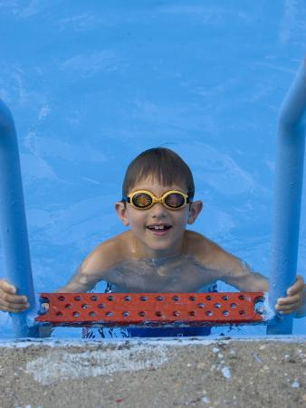 Portrait of 9 Year Old Boy in Swimming Pool, Kiamesha Lake, New York, USA