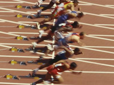 Blurred Action of Male Runners Starting a 100 Meter Sprint Race