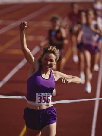 Female Runner Victorious at the Finish Line in a Track Race