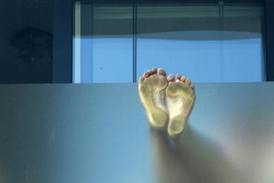 A Pair of Feet are Pressed Against Frosted Glass on a Balcony in Brighton