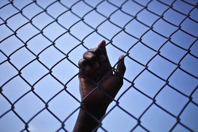 A Man Puts His Hand on a Fence During Food Distribution in Port-Au-Prince