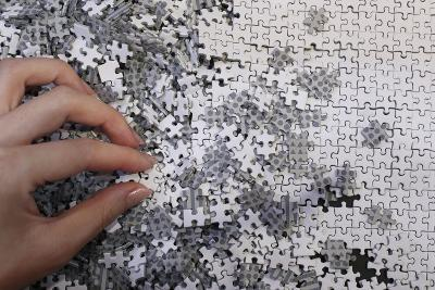 An Employee Holds a Piece of the Company's White Micro 1000 Piece Jigsaw Puzzle