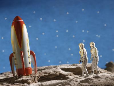 Astronaut Figurines Standing Beside Toy Rocket