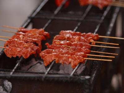 Several Skewers of Saucy Red Meat on a Grill