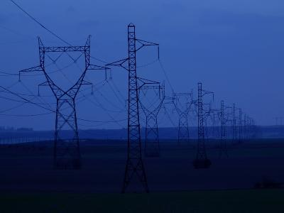 Tall Towers Supporting Power Lines in a Dark Blue Sky