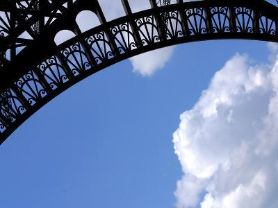 A Detailed Arch on the Eiffel Tower Against Blue Sky and Clouds
