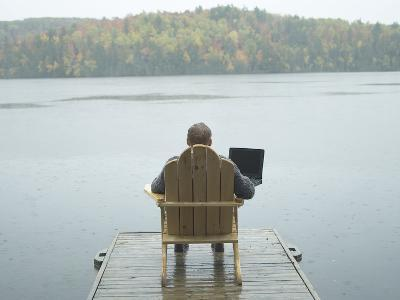 Man Sitting on a Dock Working on Laptop