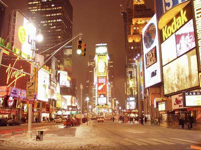 People and Cars in Snow-Filled Busy Street with Illuminating Signs in Times Square in New York City