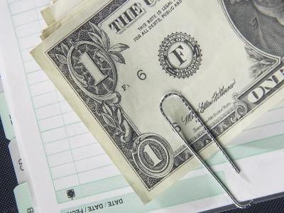 American Dollar Bill Paper Clipped to Accounting Book