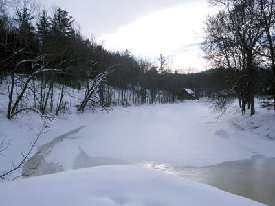Picturesque Winter Scene with a Frozen Snow Covered River Surrounded by Trees