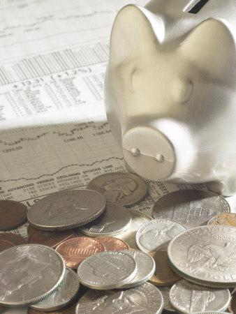 Silver Piggy Bank on Top of Pile of American Coins and Stock Market Report