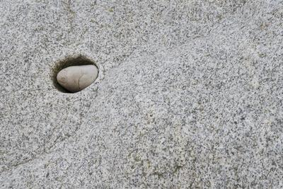 Pebble in hole of large rock, Sidmouth, Devon, England