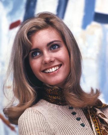 Olivia John smiling in Brown Sweater