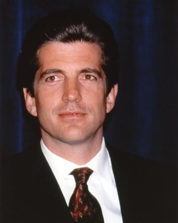 John Kennedy wearing a Black Suit and a Glossy Necktie in a Close Up Portrait