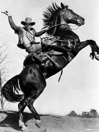 James Cagney Rode on a Black Horse in Long Sleeve Coat and Cowboy Hat with Right Hands Raise Up