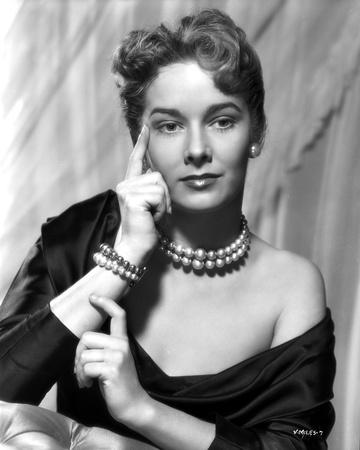 Vera Miles photographed waering a silk black, off-the-shoulder, boat neck gown, with her finger pre