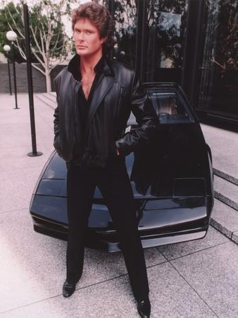 David Hasselhoff standing in Black Leather Jacket with Black Pants and Black Shoes