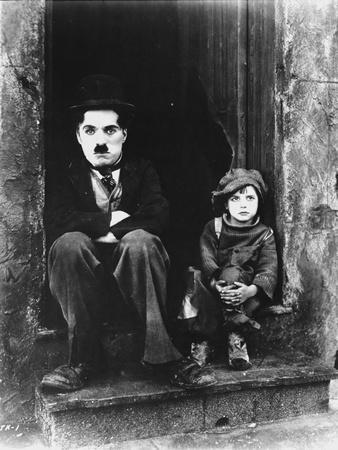 Charlie Chaplin Siting Beside Child in Black Tuxedo with Hat