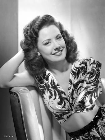 Carol Forman wearing a Printed Dress with Head Leaning on Hand