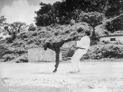 Bruce Lee in Black Attire Fighting with wearing White Attire