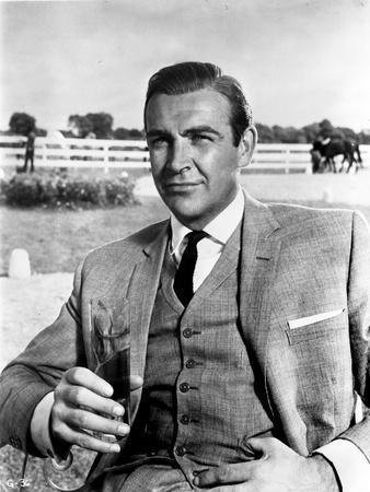 Goldfinger Man Holding Glass of Wine wearing Formal Outfit with Necktie