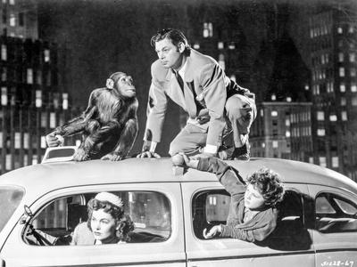 Johnny Weissmuller Riding on Top of a Car in a Classic Movie Scene