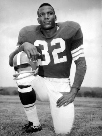 Jim Brown Kneeling in Football Attire With Helmet