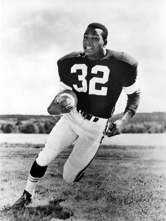 Jim Brown Playing in Football Attire With Football Ball