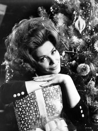 Irina Demick Leaning on Gift with Christmas Tree