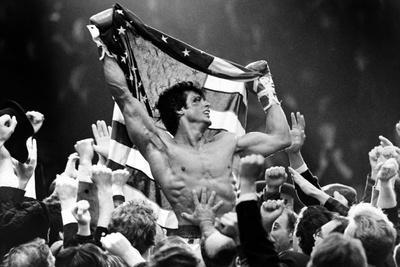 Sylvester Stallone Carried by a Men and Holding a Flag